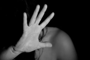 Young woman fending off a physical event of domestic violence assault, undue influence, harassment, emotional abuse, neglect